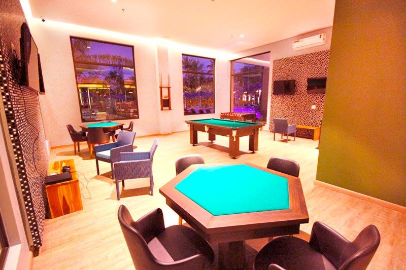 Sala de jogos com detalhes de sinuca e mesa para poker