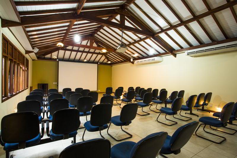 Espaço auditório com cadeiras e painel para exibição das apresentações