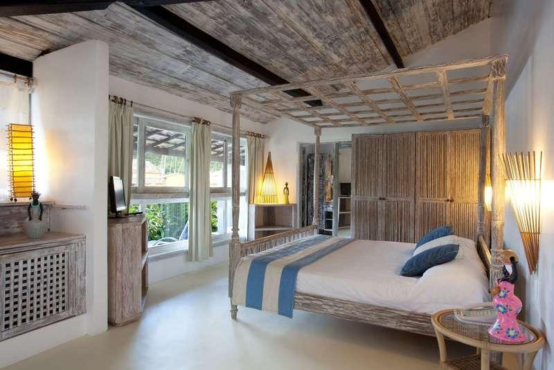 Vista acomodação lateral com cama casal e frente rio