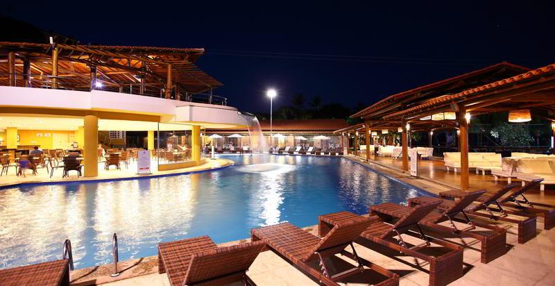 piscina com espreguiçadeiras durante a noite