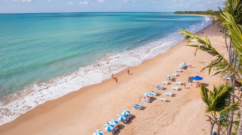 Praia com atendimento com sombra e espreguiçadeiras