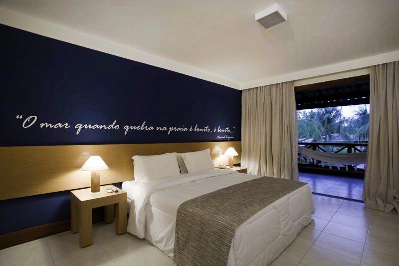 Village com detalhes azuis no fundo e cama casal
