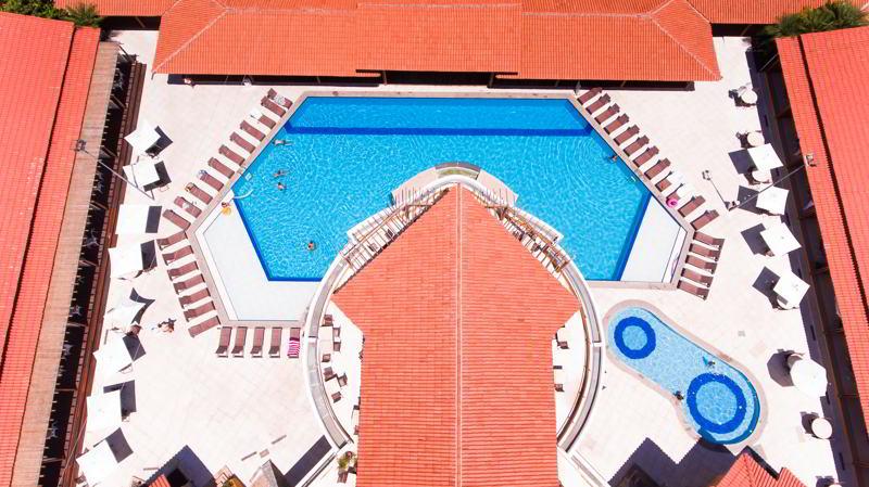 Vista aérea piscina estrutura conta com espreguiçadeiras sombra e bar molhado