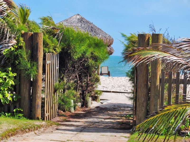 Entrada para praia com mar calmo e areia macia