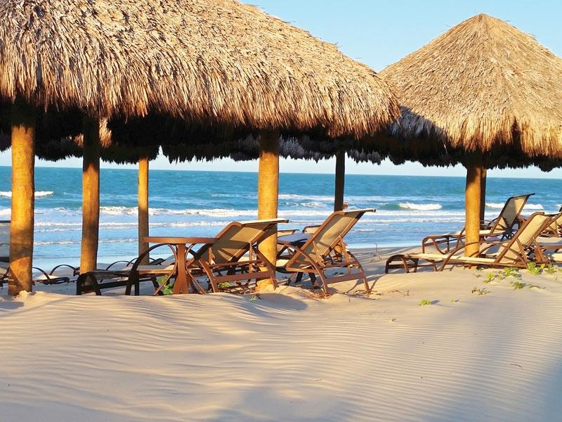 Praia com sombra dos gazebos e cadeiras